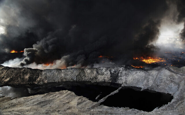 In this Oct. 4, 2016 file photo, oil fields in the town of Qayyarah burn, nearly a month after fleeing Islamic State militants set fire to the oil. (Bram Janssen/AP)