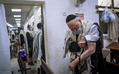 Holocaust survivor Yehoshua Datsinger places tefillin on his arm above the Auschwitz concentration camp identification number tattoo, during morning prayer at a synagogue, in Bnei Brak, Israel, September 21, 2020. (Oded Balilty/AP)
