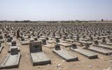 A man walks in a mass graveyard where hundreds of Yemeni fighters are buried in Marib, Yemen, June 21, 2021. (AP Photo/ Nariman El-Mofty)