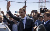 In this May 26, 2021 file photo, Syrian President Bashar Assad, center, waves to his supporters at a polling station during the Presidential elections in Douma, Syria. (AP Photo/Hassan Ammar, File)