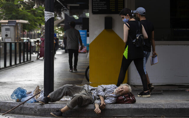 In this July 17, 2020 file photo, a woman looks at a homeless Lebanese man sleeping on the ground in Hamra street, in Beirut, Lebanon (AP Photo/Hassan Ammar, File)
