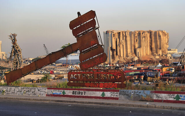 In this Aug. 4, 2021 file photo, a monument that represents justice stands in front of towering grain silos that were gutted in the massive August 2020 explosion at the port in Beirut, Lebanon (AP Photo/Hussein Malla, File)