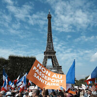 """In this September 4, 2021, file photo, a protester holds a placard reading """"No to the health pass"""" during a demonstration against the COVID-19 health pass in front of the Eiffel Tower, in Paris. (AP Photo/Thibault Camus, File)"""