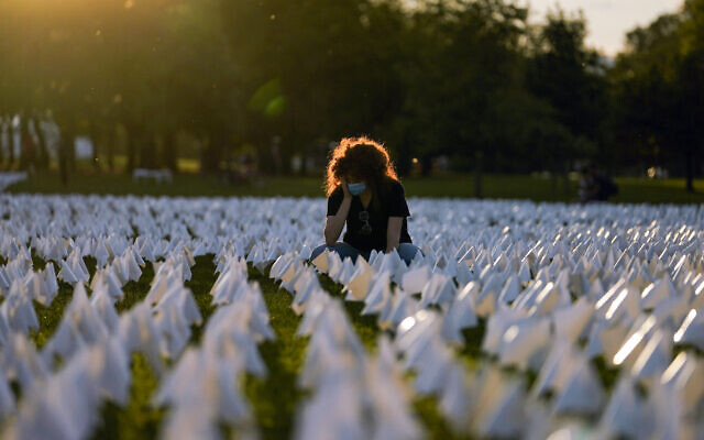 """In this Sept. 17, 2021, file photo, Zoe Nassimoff looks at white flags that are part of artist Suzanne Brennan Firstenberg's temporary art installation, """"In America: Remember,"""" in remembrance of Americans who have died of COVID-19, on the National Mall in Washington. Nassimoff's grandparents who lived in Florida died from COVID-19. (AP Photo/Brynn Anderson, File)"""