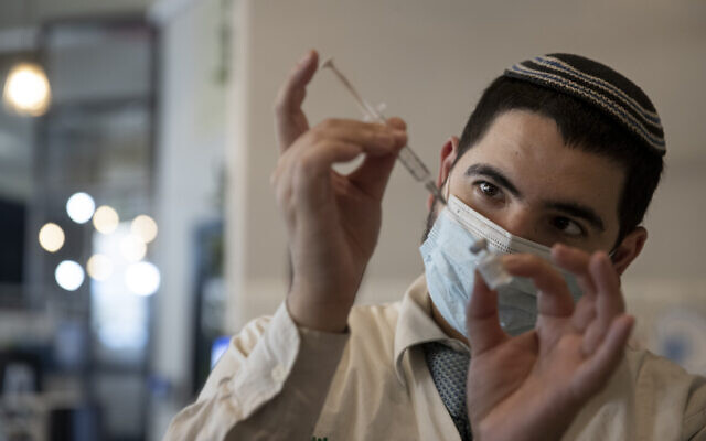 A medical worker prepares a vial of the Pfizer coronavirus vaccine at Clalit Health Service's vaccination center in the Cinema City complex in Jerusalem, September 22, 2021. (AP Photo/Maya Alleruzzo)