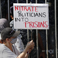 A protester holds a placard outside a court building during a demonstration of solidarity with Judge Tarek Bitar who is investigating last year's deadly seaport blast, in Beirut, Lebanon, September 29, 2021. (AP Photo/Hussein Malla)