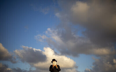An ultra-Orthodox Jewish man of the Kiryat Sanz Hasidic sect prays on a hill overlooking the Mediterranean Sea as they participate in a Tashlich ceremony, in Netanya, Israel, on Tuesday, Sept. 14, 2021. (AP Photo/Ariel Schalit)
