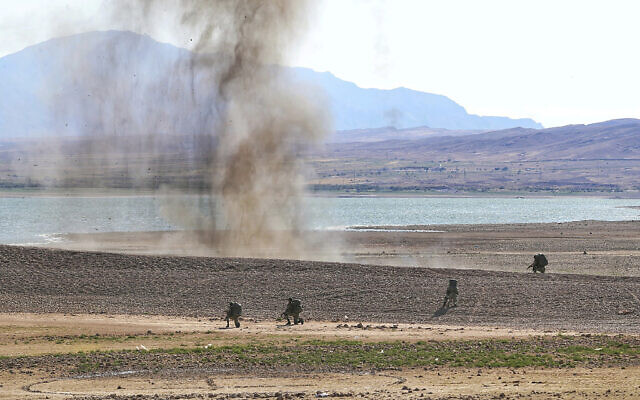 In this photo released by the official website of the Iranian Army on Friday, Oct. 1, 2021, ground force troops partake in maneuvers near the Iranian border with Azerbaijan. (Iranian Army via AP)