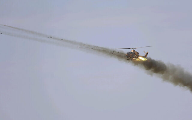 In this undated picture released by the official website of the Iranian Army on October 1, 2021, a helicopter fires in a maneuver near Iranian border with Azerbaijan. (Iranian Army via AP)