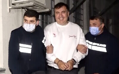 Georgian Police officers escort former President Mikheil Saakashvili after he was arrested in Rustavi, Georgia, on Friday, October 1, 2021. (Georgian Interior Ministry Press Service via AP)