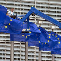 In this June 23, 2016 file photo, a worker on a lift adjusts the EU flags in front of EU headquarters in Brussels. (AP Photo/Virginia Mayo, File)