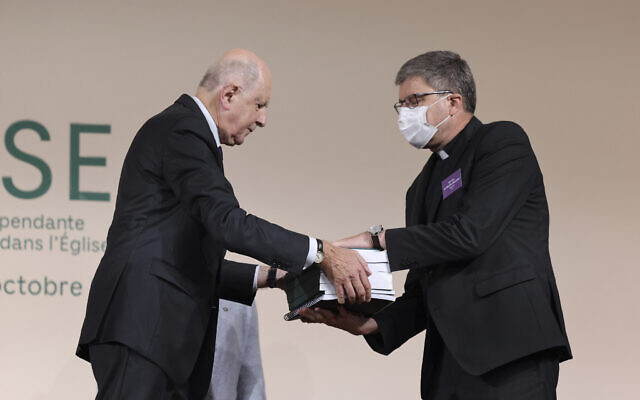 Commission president Jean-Marc Sauve, left, hands copies of the report to Catholic Bishop Eric de Moulins-Beaufort, president of the Bishops' Conference of France (CEF), during the publishing of a report by an independant commission into sexual abuse by church officials (Ciase), in Paris, October 5, 2021. (Thomas Coex, Pool via AP)