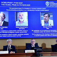Secretary General of the Royal Swedish Academy of Sciences Goran Hansson, center, flanked at left by member of the Nobel Committee for Physics Thors Hans Hansson, left, and member of the Nobel Committee for Physics John Wettlaufer, right, announces the winners of the 2021 Nobel Prize in Physics at the Royal Swedish Academy of Sciences, in Stockholm, Sweden, Tuesday, Oct. 5, 2021. (Pontus Lundahl/TT via AP)
