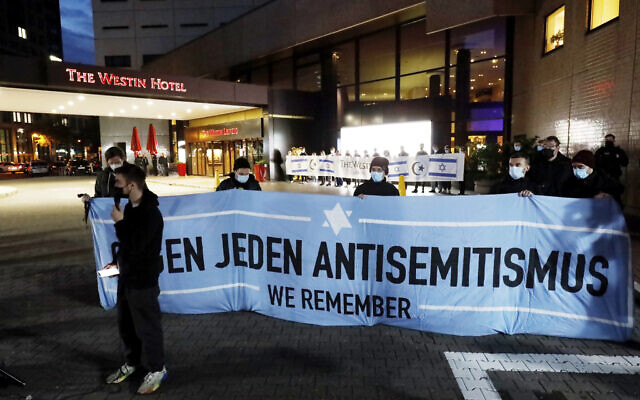 """People gather in front of the """"Westin Hotel"""" in Leipzig, Germany, on Tuesday, October 5, 2021, to show solidarity with the musician Gil Ofarim. (Dirk Knofe/dpa via AP)"""