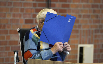 The accused Josef S. covers his face as he sits at the court room in Brandenburg, Germany, Thursday, Oct. 7, 2021. (AP Photo/Markus Schreiber)