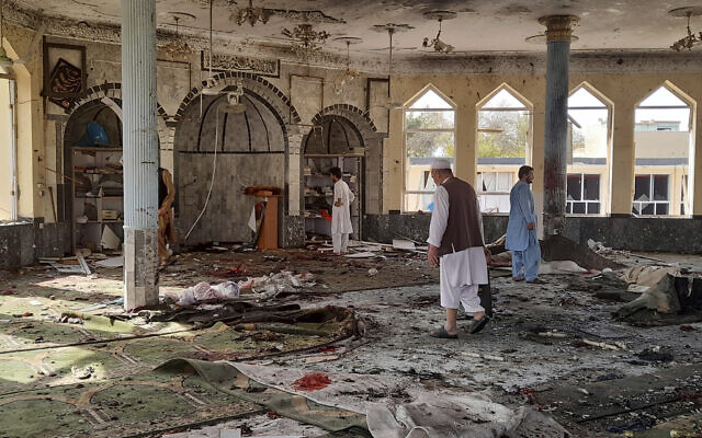 People inspect the inside of a mosque following a bombing in Kunduz province northern Afghanistan, October 8, 2021. (AP Photo/Abdullah Sahil)