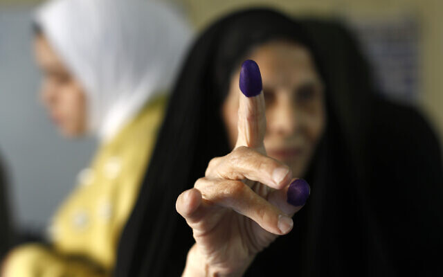 An Iraqi elderly woman shows her ink-stained finger after casting her vote inside a polling station in the country's parliamentary elections in Baghdad, Iraq, October 10, 2021. (AP Photo/Hadi Mizban)