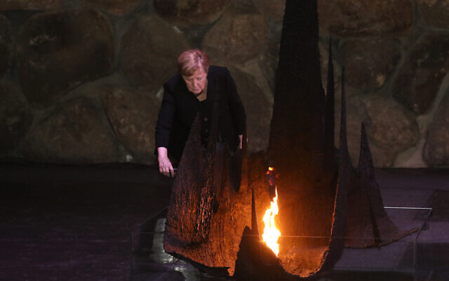 German Chancellor Angela Merkel rekindles the eternal flame at the Hall of Remembrance in the Yad Vashem Holocaust Museum in Jerusalem, Sunday, Oct. 10, 2021. (AP Photo/Ariel Schalit)