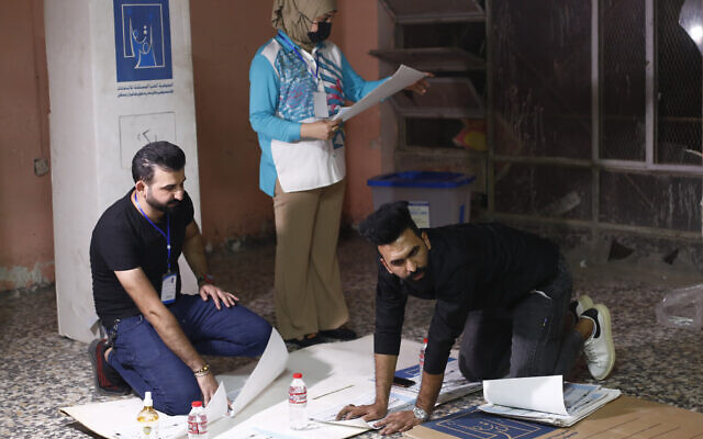 Election workers count ballots as they close a polling station at the end of voting in parliamentary elections, in Baghdad, Iraq, October 10, 2021. (AP Photo/Hadi Mizban)