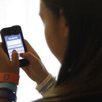 In this June 4, 2012, file photo, an unidentified 11-year-old girl logs into Facebook on her iPhone at her home in Palo Alto, Calif.  (AP Photo/Paul Sakuma, File)
