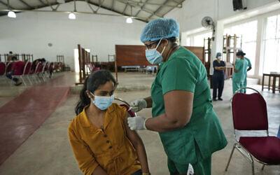 A Sri Lankan university student receives her coronavirus vaccine at the Sri Jayawardenapura university in Colombo, Sri Lanka, October 11, 2021. (Eranga Jayawardena/AP)