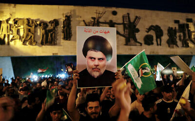 Followers of Shiite cleric Muqtada al-Sadr celebrate holding his posters, after the announcement of the results of the parliamentary elections in Tahrir Square, Baghdad, Iraq, on October 11, 2021. (AP Photo/Khalid Mohammed)