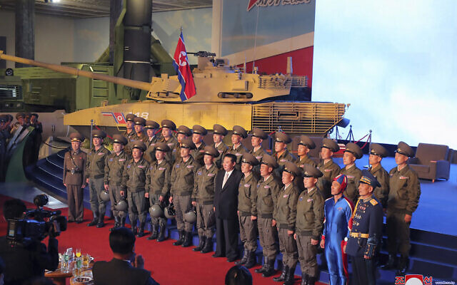In this photo provided by the North Korean government, North Korean leader Kim Jong Un, center, poses for a group photo with fighter pilots who made the demonstration flight at the opening of an exhibition of weapons systems in Pyongyang, North Korea, Monday, Oct. 11, 2021. (Korean Central News Agency/Korea News Service via AP)