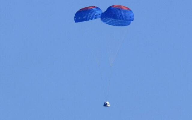 Parachutes slow the descent of the Blue Origin capsule with passengers William Shatner, Chris Boshuizen, Audrey Powers and Glen de Vries near the company's spaceport near Van Horn, Texas, Wednesday, Oct. 13, 2021. (AP Photo/LM Otero)