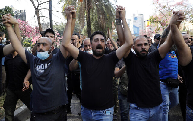 Supporters of the Shiite Hezbollah and Amal groups chant slogans against Judge Tarek Bitar who is investigating last year's deadly seaport blast, during a protest in front of the Justice Palace in Beirut, Lebanon, Thursday, Oct. 14, 2021. (AP Photo/Hussein Malla)
