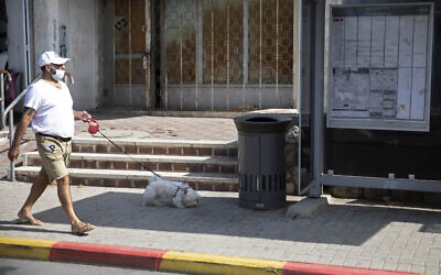 An Israeli man walks a dog near a trashcan installed next to a bus stop that applauds to those who use it, in Jerusalem, Thursday, Oct. 14, 2021. (AP Photo/Sebastian Scheiner)