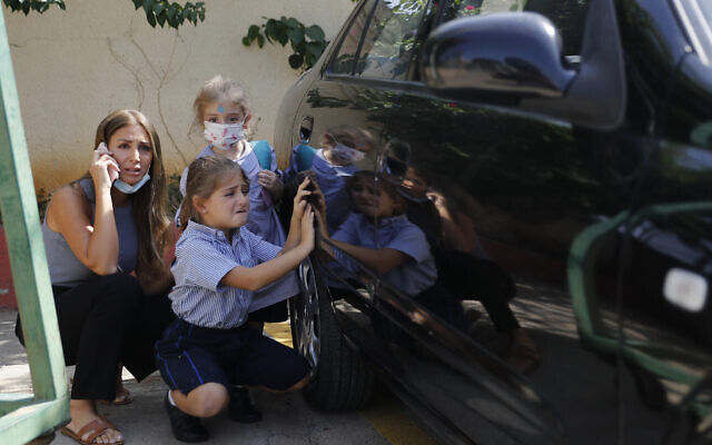 A Lebanese mother with her children hide behind a car from sniper fire outside a school, in the Christian neighborhood of Ain el-Remaneh, in Beirut, Lebanon, on October 14, 2021. (AP Photo/Hussein Malla)