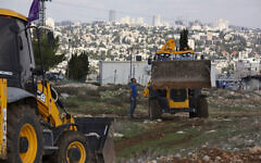 In this Nov. 16, 2020, file, photo, workers take a break before European Union officials visit the construction site for the Givat Hamatos neighborhood in East Jerusalem. (AP Photo/Maya Alleruzzo, File)