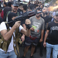 Supporters of the Shiite Amal group fire weapons in the air during the funeral processions of Hassan Jamil Nehmeh, who was killed during clashes, in the southern Beirut suburb of Dahiyeh, Lebanon, Friday, Oct. 15, 2021.  (AP Photo/Bilal Hussein)