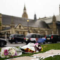 Flowers are placed as a tribute in Parliament Square following Friday's death of member of Parliament David Amess in Leigh-on-Sea, Essex, in London, on October 16, 2021. (Aaron Chown/PA via AP)