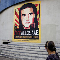 A pedestrians walks near a poster asking for the freedom of Colombian businessman and Venezuelan special envoy Alex Saab, in Caracas, Venezuela, October 16, 2021. (Ariana Cubillos/AP)