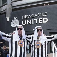 Newcastle fans pose for a photo outside the ground before an English Premier League soccer match between Newcastle and Tottenham Hotspur at St. James' Park in Newcastle, England, on October 17, 2021. (AP Photo/Jon Super)