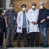 Former US president Bill Clinton (second from right) and former first lady and former US Secretary of State Hillary Clinton (right) thank Alpesh N. Amin, MD (third from left) and the medical staff as he is released from the University of California Irvine Medical Center in Orange, California, October 17, 2021. (AP Photo/Damian Dovarganes)