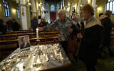 Candles are lit next to a portrait of British Lawmaker David Amess during a vigil for him at St Michaels Church, in Leigh-on-Sea, England, Sunday, Oct. 17, 2021. Amess was killed on Friday during a meeting with constituents at Belfairs Methodist church, in Leigh-on-Sea, Essex, England. (AP Photo/Alastair Grant)