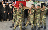 Volunteers from the Baath battalions carry the Syrian flag-wrapped coffin of Midhat as-Saleh, allegedly shot by Israeli sniper fire, in Ain Eltinah, a village along the Israeli border in the Golan Heights, during his funeral procession in Jaramana, southeast of Damascus, Syria, October 18, 2021. (AP Photo)
