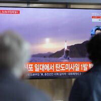People watch a TV screen showing a news program reporting about North Korea's missile launch with file footage at a train station in Seoul, South Korea, October 19, 2021. (Lee Jin-man/AP)