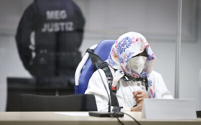 The 96-year-old defendant Irmgard F. sits in an ambulance chair behind a plexiglass screen in a courtroom in Itzehoe, Germany, Oct. 19, 2021 (Christian Charisius/DPA via AP, Pool)