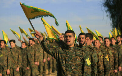Hezbollah fighters hold flags as they attend the memorial of their slain leader Sheik Abbas al-Mousawi, who was killed by an Israeli airstrike in 1992, in Tefahta village, south Lebanon, February 13, 2016. (AP Photo/Mohammed Zaatari, File)