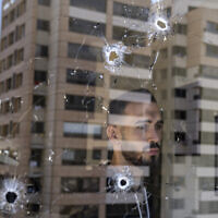 An employee looks through an office window riddled with bullet holes after the deadly clashes that erupted a week earlier along a former 1975-90 civil war front-line between Muslim Shiite and Christian areas, in Ain el-Rumaneh neighborhood, Beirut, Lebanon, October 19, 2021. (AP Photo/Hassan Ammar)