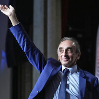 """Hard-right political talk-show star Eric Zemmour acknowledges applauses as he arrived on stage during a meeting to promote his latest book """"La France n'a pas dit son dernier mot"""" (France has not yet said its last word) in Versailles, west of Paris, Tuesday, Oct. 19, 2021. (AP Photo/Michel Euler)"""