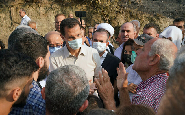 In this file photo released October 13, 2020, on the official Facebook page of the Syrian Presidency, Syrian President Bashar Assad (center left), wearing a mask to help prevent the spread of the coronavirus, speaks with people during his tour of areas that suffered heavy damage from deadly wildfires, in the Syrian coastal province of Latakia. (Syrian Presidency via Facebook via AP, File)