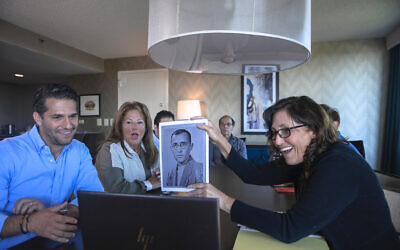 Anna Salton Eisen holds up a photo of Emil Ringel, father of Barbara Ringel, for a Zoom video call during a gathering for families of Holocaust survivors in East Brunswick, NJ, on September 26, 2021. (AP Photo/Brittainy Newman)