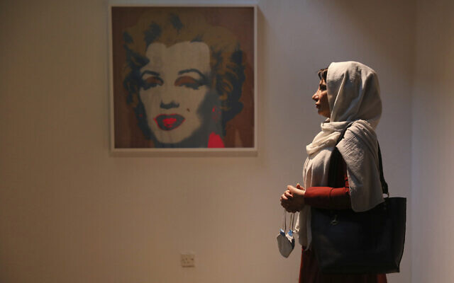 Fatemeh Rezaei, a retired teacher, stands next to a Marilyn Monroe portrait by American artist Andy Warhol at Tehran Museum of Contemporary Art in Tehran, Iran, on October 19, 2021. (AP Photo/Vahid Salemi)