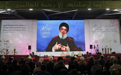 Hezbollah leader Hassan Nasrallah speaks via a video link from a secret location through a giant screen, during a ceremony marking Prophet Muhammad's birthday, in the southern suburb of Beirut, Lebanon, Friday, Oct. 22, 2021. (AP Photo/Hussein Malla)