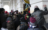 In this Jan. 6, 2021 file photo insurrectionists loyal to President Donald Trump try to open a door of the U.S. Capitol as they riot in Washington. (AP Photo/Jose Luis Magana, File)