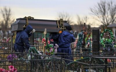 Gravediggers carry a coffin with a body of a patient who died of coronavirus at the Novo-Yuzhnoye cemetery, which serves as one of the burial grounds for those who died of the coronavirus outside Omsk, Russia, Oct. 22, 2021 (AP Photo)